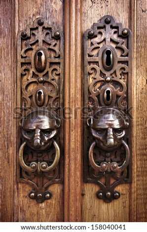 Two door knobs with knocking rings and animal heads in wooden doors - stock photo