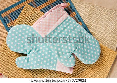 Two dotted kitchen oven gloves or mittens lying on mats, green pink spotted material, safety cloth to protect hands from hot, body protection kitchen accessory, horizontal orientation, nobody.  - stock photo