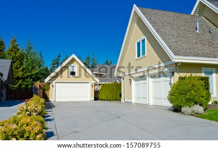 Two double doors garages with long driveway in the suburbs of Vancouver, Canada. - stock photo