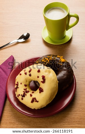 two doughnuts on a marsala plate and green coffee mug on table - stock photo