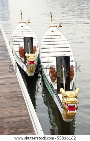 Two dragon boats tied up at jetty ready to race - stock photo