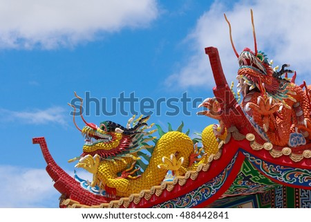 Two Dragon Statue on The Roof in The Chinese Temple with The Blue Sky