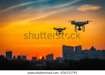 Two drone quad copters with high resolution digital camera flying aerial over spectacular sunset orange sky. Cityscape silhouette with sun goes down in the background.Vehicle at sundown and copy space