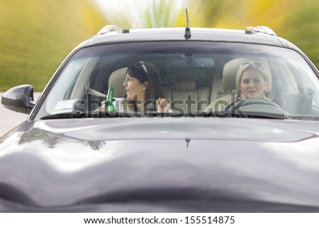Two drunk female friends driving a car as they return from a party laughing and drinking alcohol from a bottle - stock photo