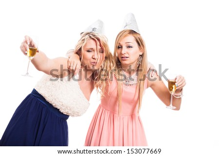 Two drunk women celebrate with alcohol, isolated on white background - stock photo