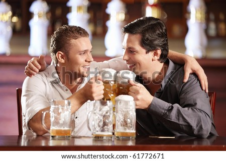 Two drunken gay men with a beer in a pub - stock photo