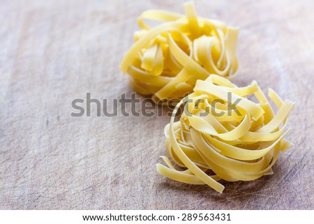 Two dry tagliatelle nests on a wooden background with copy space - stock photo