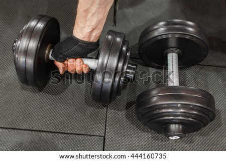 Two dumbbells on gym floor, one is held by mans hand. Top view on male athlete taking one dumbbell from set on gym floor. Pumping iron athlete hand, some free space