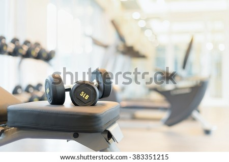 Two dumbbells on the exercise bench. Gym equipment. - stock photo