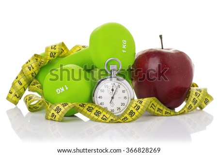 Two dumbbells, red apple and measuring and a stopwatch tape isolated on white background