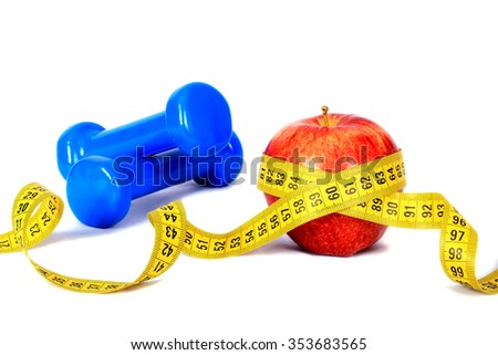 Two dumbbells, red apple and measuring tape isolated on white background. Diet concept.