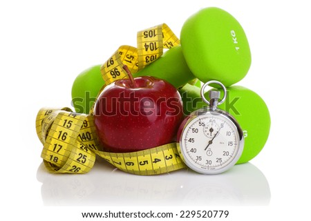 Two dumbbells, red apple, measuring tape and a stopwatch isolated on white background. Diet concept. - stock photo