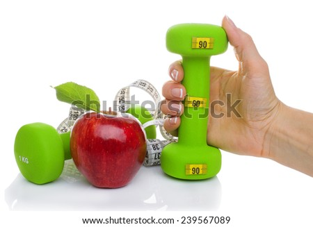 Two dumbbells, red apple, measuring tape isolated on white background. Diet concept - stock photo