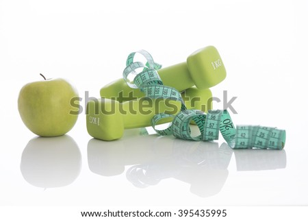 Two dumbbells with green apple and measuring tape on white background. Diet concept. - stock photo