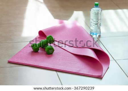 Two dumbbells with mineral water on yoga mat, healthy  lifestyle concept - stock photo