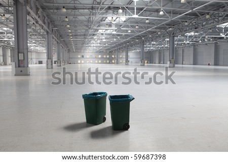 Two dustbins in large modern storehouse - stock photo