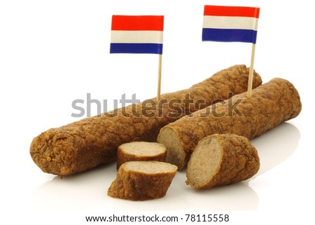 "Two Dutch snacks called ""fricandel"" with Dutch flag toothpicks and some cut pieces on a white background - stock photo"