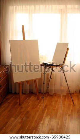 Two Easels with canvas in interior - stock photo
