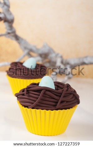 Two easter eggs cupcakes with bird nest and little blue egg. - stock photo