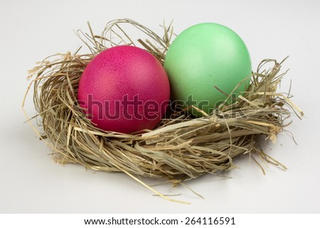 two easter eggs green and pink in nest isolated on white background  - stock photo