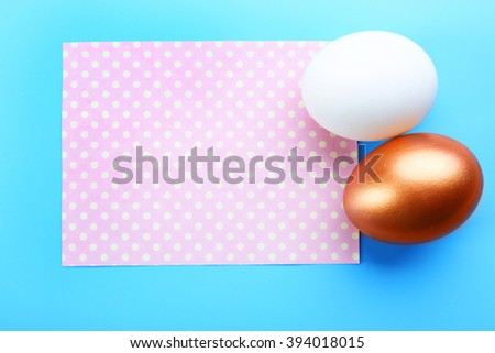 Two Easter eggs with greeting card on blue background - stock photo