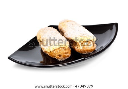 two eclairs on black dish isolated on white background