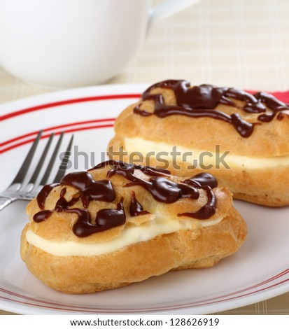 Two eclairs with chocolate icing and creamy filling on a plate