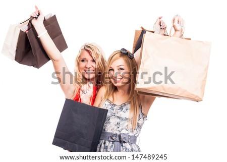 Two ecstatic girls holding shopping bags, isolated on white background - stock photo