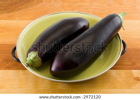 Two Eggplants in an Green Enameled Metal Bowl on Wood Table - stock photo
