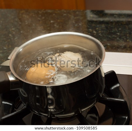 Two eggs in boiling water in stainless steel pan on gas hob - stock photo