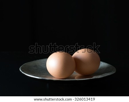 Two eggs on a plate, low, sidelit for effect.