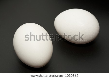 Two eggs on black background - stock photo
