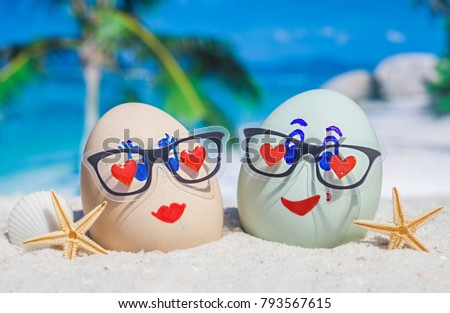 Two  eggs with faces on beach
