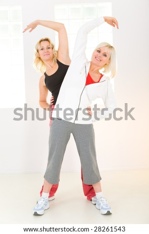 Two elder women exercising. They're smiling and looking at camera. Front viev. - stock photo