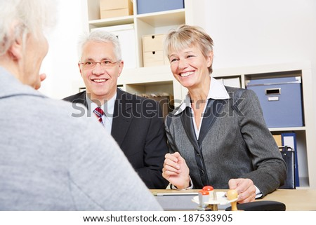 Two elderly business people talking about finances with senior woman - stock photo