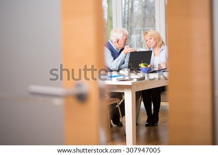 Two elderly businesspeople talking about work - stock photo