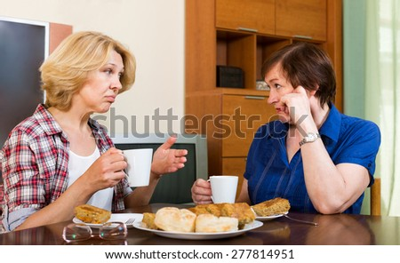 Two elderly colleagues discussing problems at work and drinking tea - stock photo
