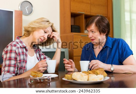 Two elderly colleagues drink tea with cake and talking - stock photo