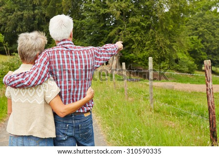 Two elderly farmers on farm pointint to field with fence - stock photo