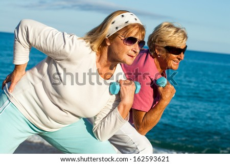 Two elderly fitness girlfriends working out together on beach.