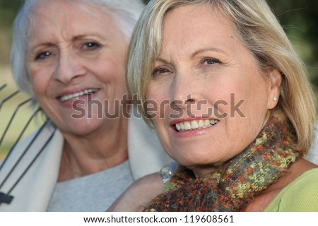 Two elderly ladies sat in the garden together - stock photo
