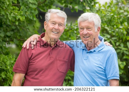 Two elderly men are embracing each other, looking into the camera and are having a good time - stock photo