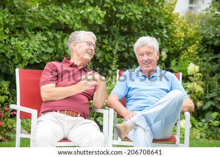 Two elderly men are sitting and enjoying the time together - stock photo