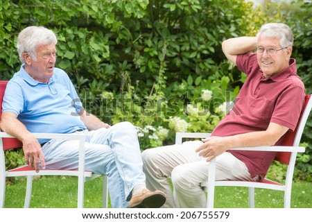Two elderly men are sitting opposite and looking into the camera expectantly, the left one looks to the right one - stock photo