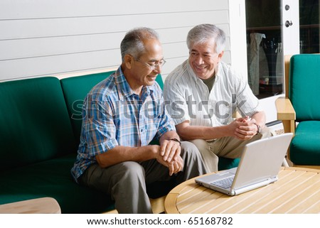 Two elderly men sitting with laptop - stock photo