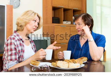 Two elderly woman with cup of tea talking at home - stock photo