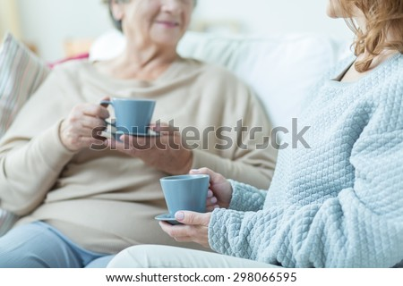 Two elderly women drinking coffee during conversation at home - stock photo