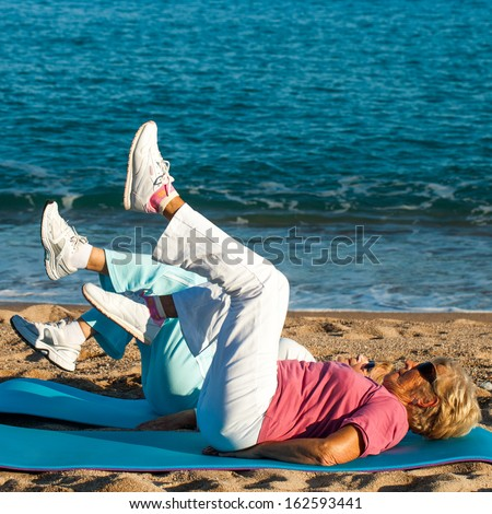 Two elderly women exercising legs together on beach. - stock photo