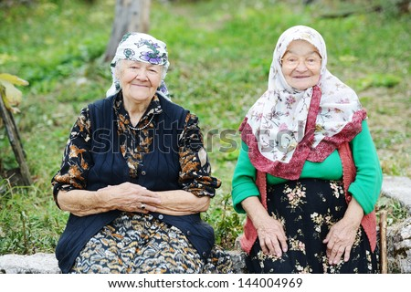 Two elderly women sitting outdoors - stock photo