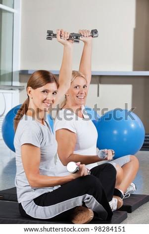 Two elderly women using dumbbells in fitness center on gym mats - stock photo